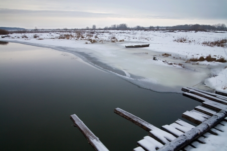 Bank of the river covered with snow and a wooden boat photo