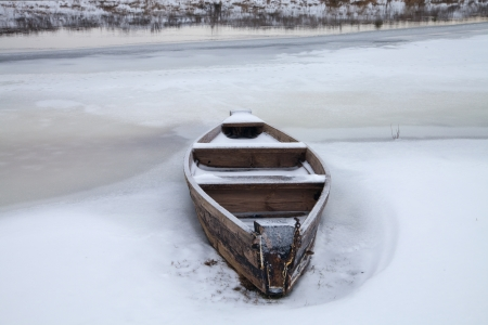 Wooden boat on the river in winter photo