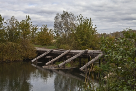 Wooden bridge over a small river photo