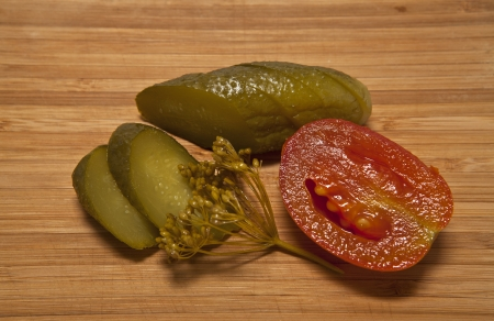 Pickled cucumbers and tomatoes on a cutting board photo