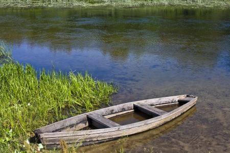 Wooden boat on the bank of a small river