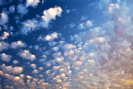Many small white clouds in the blue sky during sunset Stock Photo