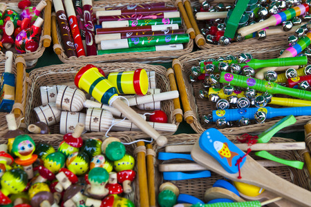 Many small wooden rattles of different colors in a wicker basket