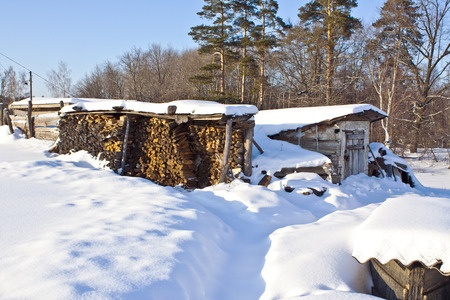 old barn in winter: View of the warehouse of wood and an old wooden barn in winter in the village Stock Photo