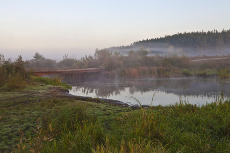 Wooden bridge over a small river in the mist at sunrise Stock Photo