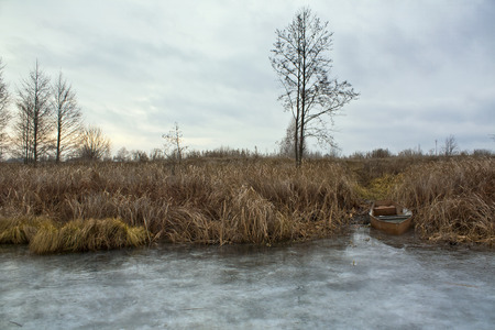 Old boat on the shore of a frozen lake in the fall