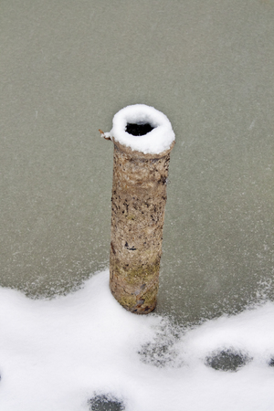 A piece of old rusty pipes frozen in the ice is photographed close up