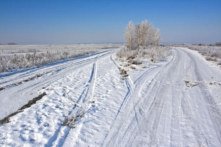 Dirt road on a snowy field in late winter Stock Photo