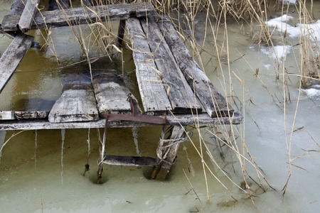 Old ruined wooden platform for fishing frozen into the ice Stock Photo