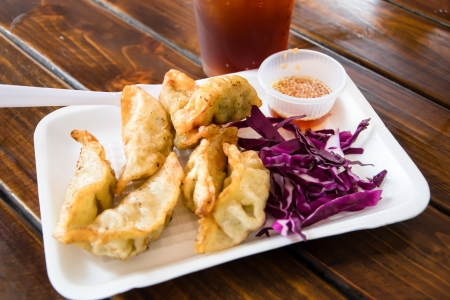 Pan Fried Dumpling with sauce on wood table photo