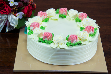 Birthday cake with flowers on wood table