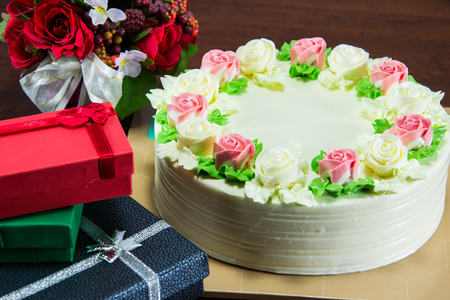Birthday cake with flowers and gift on wood table photo