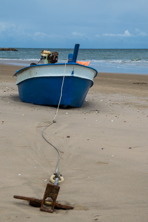 Small rusty anchor and boat on the beach photo