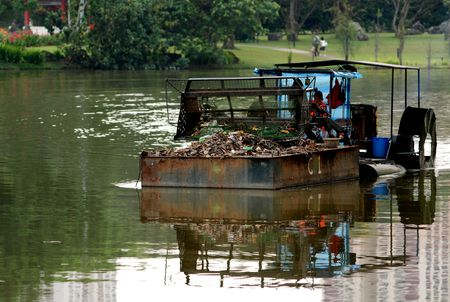 tug boat: tug boat carrying rubbish to shore in the lakes
