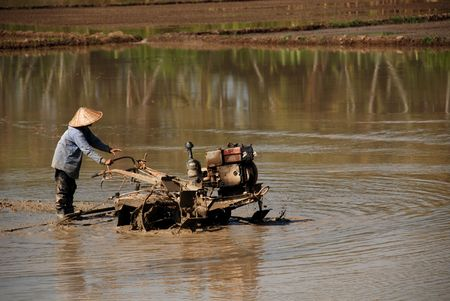 plough: a farmer driving a plough machine in the paddy field Stock Photo