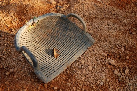 winnowing: dustpan and earth at the work place  Stock Photo