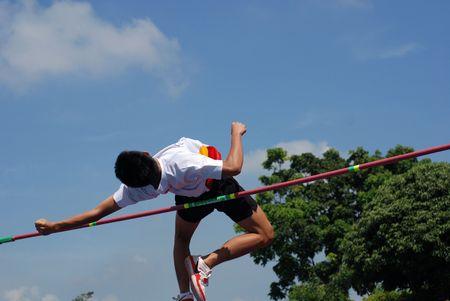 Een man sprong over de balk Stockfoto