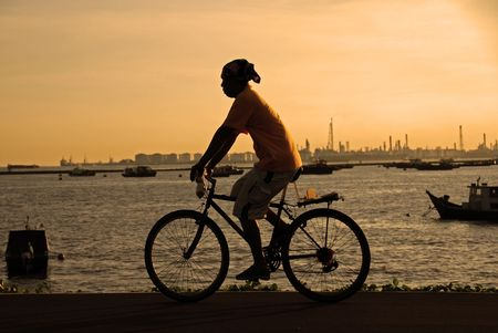 sunset and man cycling at the seaside photo