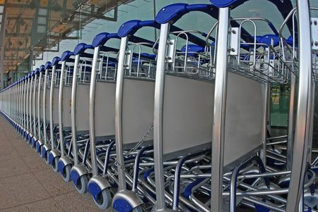 conveyor rail: row of trolley and tinted glass at the airport