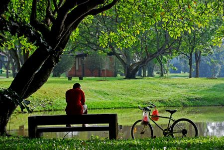man and bicycle take a rest in the parks Stock Photo