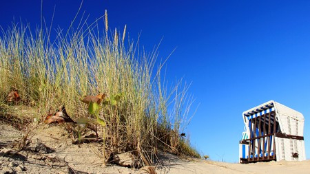 One beach chair with blue sky and autumn mood by baltic seaside