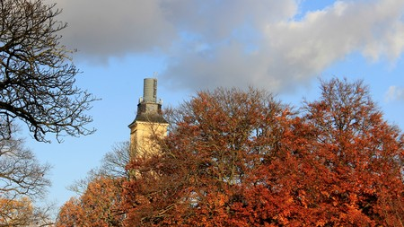 High Tower And Autumn Leaves With Cloudy Sky In Hannover Germany