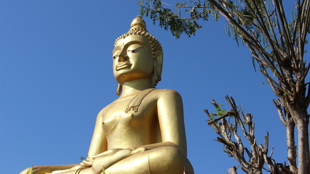Golden big buddha with blue sky background. happiness and peace in Thailand