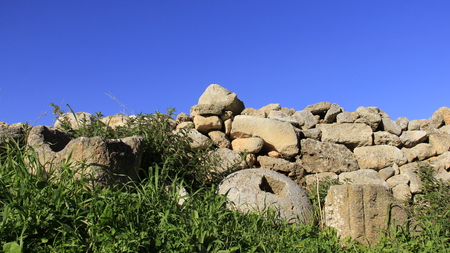 Stone wall with green grass and blue sky background  on Crete island Greece Stock Photo