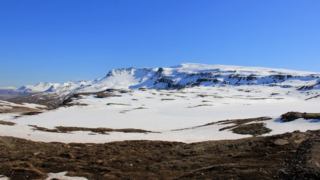 Rocky mountain and valley covered with snow and ice winter landscape with clear sky in sunny. Iceland