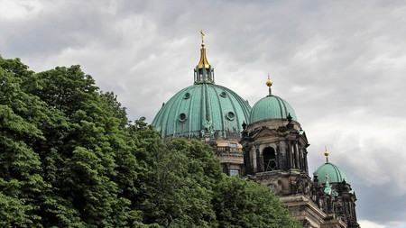 Berlin cathedrals with golden cross and rain clouds in sunmertime.Germany