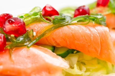 Salade van verse groenten met zalm vis is versierd met zeewier chukka en granen van granaatappel close-up