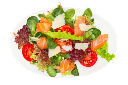 plantaardige salade met zalm en Parmezaanse kaas op wit wordt geïsoleerd