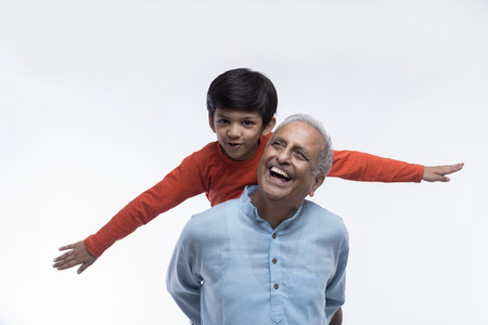 Boy sitting on grandfather's shoulders with arms outstretched Standard-Bild