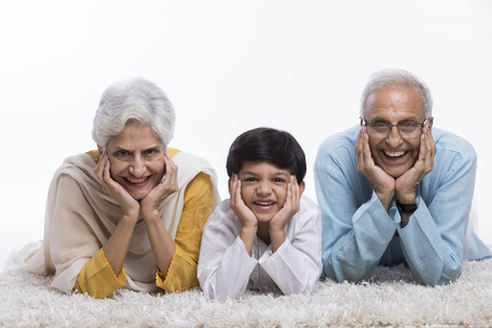 Grandparents and grandson lying on carpet with hand on chin 스톡 콘텐츠