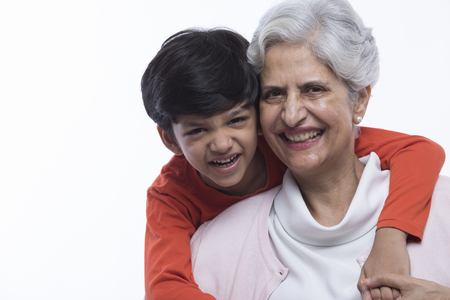 Portrait of happy grandmother and grandson hugging Stock Photo