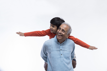 Boy sitting on grandfathers shoulders pretending to be flying