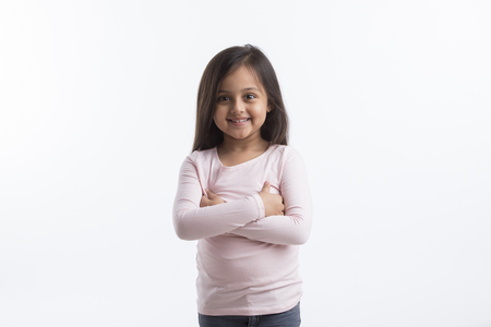 Portrait of  happy little girl standing with her arms crossed