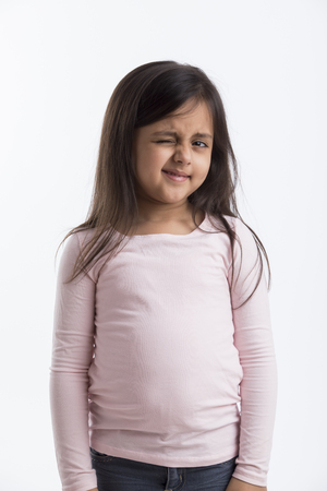 Little girl in pink top and jeans winking her eye standing against a white background.