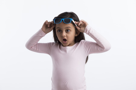 Little girl giving a surprised look putting her goggles on her head. Banco de Imagens