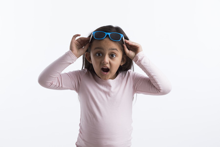 Little girl giving a surprised look putting her goggles on her head. Archivio Fotografico