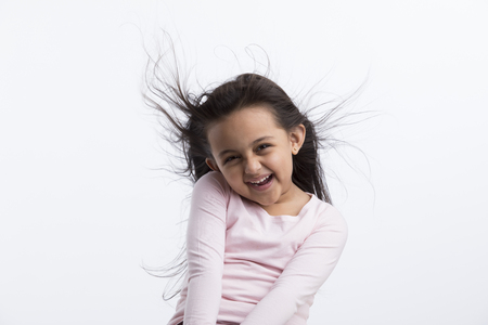 Small girl laughing as her hair fly due to air. Archivio Fotografico