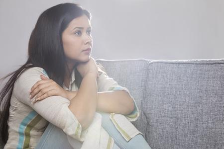 Portrait of woman sitting on sofa Banco de Imagens