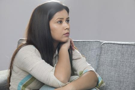 Portrait of serious woman sitting on sofa Banco de Imagens