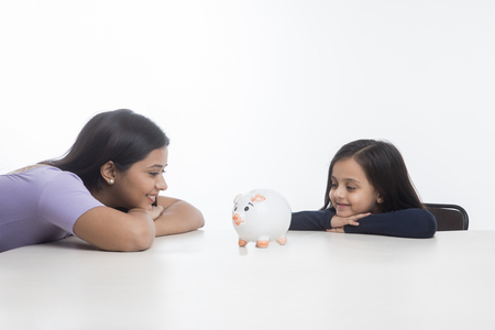 Mother and daughter leaning on table and looking at piggy bank Archivio Fotografico
