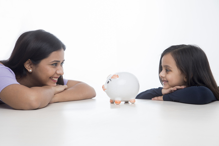 Happy mother and daughter leaning on table and looking at piggy bank