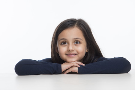 Portrait of little girl leaning on table and looking up