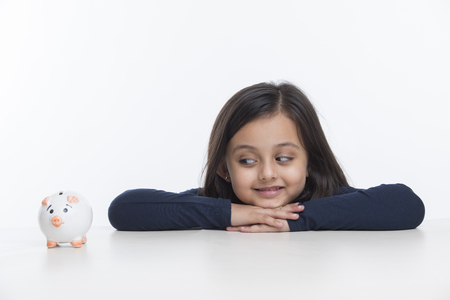 Portrait of little girl leaning on table and looking at piggy bank