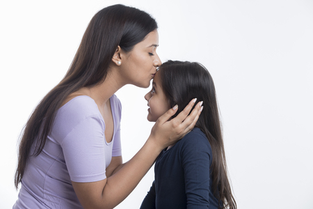 Mother kissing daughter on forehead Archivio Fotografico