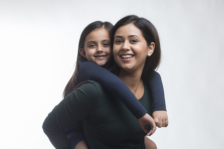 Portrait of mother giving daughter piggyback ride