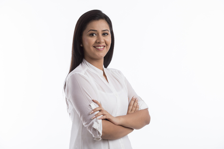 Portrait of smiling woman wearing white top standing arms crossed